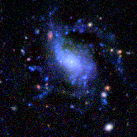 very small nucleus, can see a distant red galaxy through the disk.